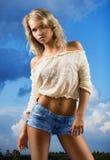 Muchacha en pantalones cortos en un fondo del cielo. Imagen de archivo libre de regalías