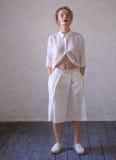 Muchacha en pantalones cortos y camisa blancos largos Fotos de archivo