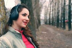 Muchacha en parque con el auricular Fotos de archivo libres de regalías