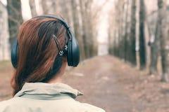 Muchacha en parque con el auricular Fotos de archivo