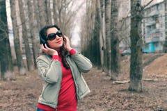 Muchacha en parque con el auricular Imagen de archivo libre de regalías