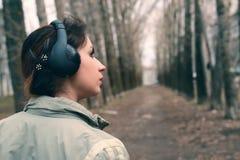 Muchacha en parque con el auricular Imagen de archivo