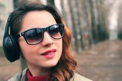 Muchacha en parque con el auricular Fotografía de archivo