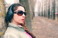 Muchacha en parque con el auricular Foto de archivo libre de regalías