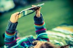 Muchacha en parque con la tableta Imagenes de archivo