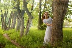 Muchacha en parque del cuento de hadas con el árbol en primavera Fotografía de archivo