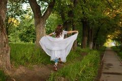 Muchacha en parque del cuento de hadas con el árbol en primavera Imagenes de archivo