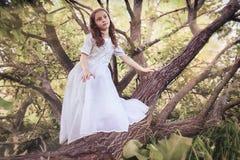 Muchacha en parque del cuento de hadas con el árbol en primavera Foto de archivo libre de regalías
