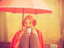 Muchacha en parque del otoño que disfruta de la bebida caliente Imagen de archivo