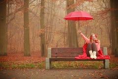 Muchacha en parque del otoño que disfruta de la bebida caliente Imágenes de archivo libres de regalías