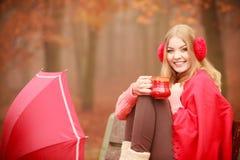 Muchacha en parque del otoño que disfruta de la bebida caliente Fotografía de archivo
