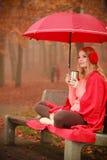 Muchacha en parque del otoño que disfruta de la bebida caliente Fotos de archivo libres de regalías