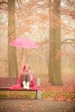 Muchacha en parque del otoño que disfruta de la bebida caliente Fotografía de archivo libre de regalías