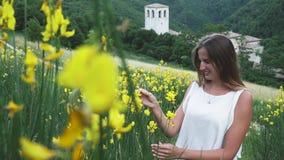 Muchacha en paseos de los pantalones cortos entre las flores del alforfón almacen de video