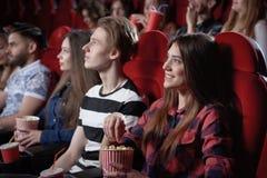 Muchacha en película interesante de observación de la camisa roja en el cine fotos de archivo libres de regalías
