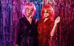 Muchacha en pelucas y vestidos atractivos elegantes con las lentejuelas, en la luz de neón de un disco Celebre, diviértase, cel fotos de archivo