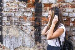muchacha en perfil contra una pared de ladrillo que escucha la música en auriculares Fotografía de archivo libre de regalías