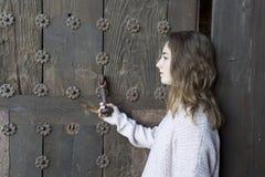 Muchacha en perfil en un fondo de una puerta vieja Fotos de archivo