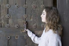 Muchacha en perfil en un fondo de una puerta vieja Fotografía de archivo libre de regalías