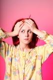 Muchacha en pijamas amarillos con dolor de cabeza Fotografía de archivo libre de regalías