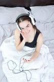 Muchacha en pijamas con reproductor Mp3 o el enjoyin del móvil y de los auriculares Fotos de archivo