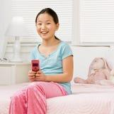 Muchacha en pijamas en envío de mensajes de texto del dormitorio Imagenes de archivo