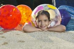 Muchacha en piscina con las pelotas de playa Foto de archivo libre de regalías