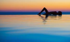 Muchacha en piscina del infinito de la puesta del sol imagenes de archivo