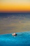 Muchacha en piscina del infinito de la puesta del sol Imágenes de archivo libres de regalías