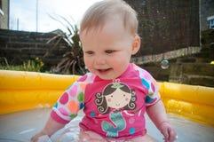 Muchacha (1) en piscina inflable amarilla y rashie rosado Imágenes de archivo libres de regalías