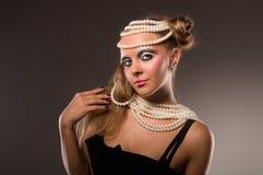 Muchacha en poca alineada y perla negras Imagen de archivo