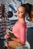 Muchacha en prensa de banco de la barra de la gimnasia Foto de archivo libre de regalías