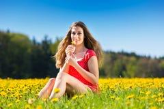 Muchacha en primavera en un prado de la flor con el diente de león imagen de archivo