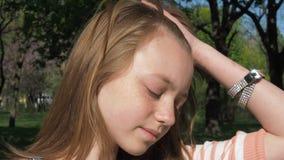 Muchacha en primer de las gafas de sol Un adolescente con las pecas saca los vidrios en naturaleza Manos en pulseras almacen de metraje de vídeo