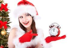 Muchacha en punta del sombrero de santa en el reloj de alarma. Imágenes de archivo libres de regalías