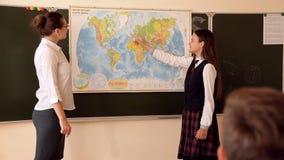 Muchacha en respuestas uniformes de un tablero en la lección de la geografía almacen de video