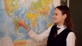 Muchacha en respuestas uniformes de un tablero en la lección de la geografía almacen de metraje de vídeo