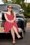 Muchacha en rojo con el coche de la vendimia Foto de archivo