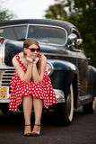 Muchacha en rojo con el coche de la vendimia Fotos de archivo
