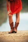 Muchacha en rojo con las botas de vaquero Fotografía de archivo