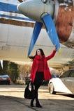 Muchacha en rojo en un fondo del aeroplano viejo Foto de archivo libre de regalías