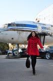 Muchacha en rojo en un fondo del aeroplano viejo Fotos de archivo