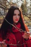 Muchacha en rojo entre las ramas desnudas de árboles Imagen de archivo libre de regalías