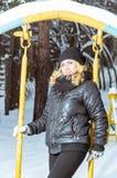 Muchacha en ropa caliente negra en el bosque del invierno en un paseo Imágenes de archivo libres de regalías