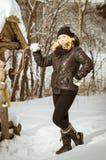 Muchacha en ropa caliente negra en el bosque del invierno en un paseo Imagenes de archivo