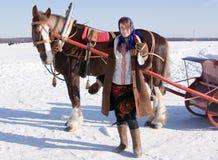 Muchacha en ropa tradicional y traído por caballo imagen de archivo