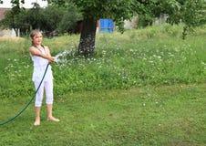 Muchacha en salpicar blanco con la manguera de jardín Foto de archivo libre de regalías