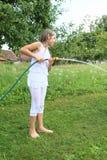 Muchacha en salpicar blanco con la manguera de jardín Fotografía de archivo libre de regalías