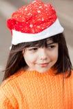 Muchacha en Santa Hat Looking Away Foto de archivo libre de regalías