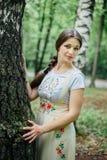 Muchacha en sarafan ruso tradicional del vestido inclinada contra abedul Imagen de archivo libre de regalías